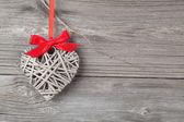 Jedno srdce s červenou mašli, na dřevěné pozadí — Stock fotografie