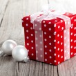 Red gift box, polka dots, on wood background — Stock Photo