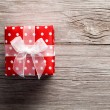 Red gift box, polka dots, on wood background — Stock Photo #36573069