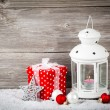 Burning lantern in the snow with christmas decoration, on wood b — Stock Photo
