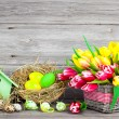 Easter decoration with eggs, birdhouse and tulips. wooden backgr — Stock Photo