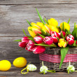 Spring tulips in wooden basket with Easter eggs, on wooden backg — Stock Photo #41039355