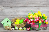 Easter decoration with eggs, birdhouse and tulips. wooden backgr — Zdjęcie stockowe