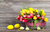 spring tulips in wooden basket with Easter eggs, on wooden backg — Stock Photo