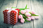 Beautiful tulips with red polka-dot gift box. happy mothers day, — Stock Photo