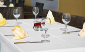 Cafe terrace with dinner table place setting: napkin & wineglass — Stock Photo