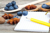 Notebook and pencil with ingredients food on wooden table — Stock Photo