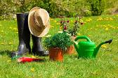 Trädgårdsredskap och en stråhatt på gräset i trädgården — Stockfoto