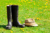 Garden boots and straw hat on the grass in the garden — Stockfoto