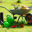 Gardening tools and a straw hat on the grass in the garden — Stock Photo