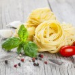 Italian pasta fettuccine nest with garlic, tomatoes and fresh ba — Stock Photo