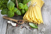 Spaghetti with garlic, peppers, and fresh basil leaves on wooden — Stock Photo