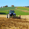 Farm tractor on the field working, plowing land — Stock Photo #49644655