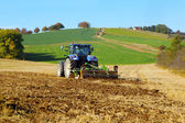 Farm tractor on the field working, plowing land — Foto de Stock