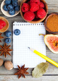 Top view of recipe book with ingredients on wooden table — Stock Photo
