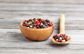 Colored Pepper in the wooden bowl, on wooden board — Stock Photo