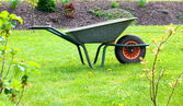 Garden-wheelbarrow on green grass — Stock Photo