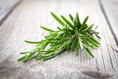Twigs of rosemary on wooden texture — Stock Photo