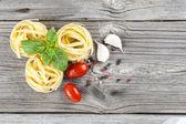 Italian pasta fettuccine nest with garlic, tomatoes and fresh ba — Stok fotoğraf