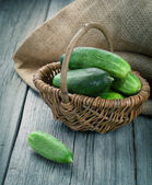 Harvest cucumbers in a basket on the wooden background — Stock Photo