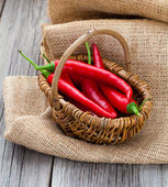 Red chili pepper in a wicker basket with burlap on the wooden ba — Zdjęcie stockowe