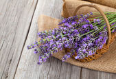 Lavender flowers in a basket with burlap on the wooden backgrou — ストック写真