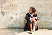 Boy sitting in front of a wall — Stock Photo