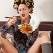 Stock Photo: Sexy girl eating spaghetti on the couch
