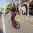 Business woman drink a coffee on the unicycle — Stock Photo
