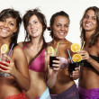 Four girls fun with a drink, portrait in studio, isolated on white background — Stock Photo #29997335
