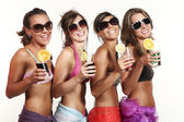 Four girls fun with a drink, portrait in studio, isolated on white background — Stock Photo
