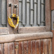 Closed lock with yellow chain on an old wooden door — Stock Photo
