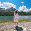 Girl on the shore of a mountain lake — Stock Photo #39826483