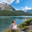 Girl on the shore of a mountain lake — Stock Photo