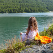 Girl on the shore of a mountain lake — Stock Photo #39835765