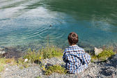 Boy on the shore of a mountain lake — Stock Photo