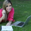 Young student outside in the park with computer and notebook st — Stock Photo