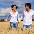 Happy couple running in a field smiling and holding hands under blue sky — Stock Photo