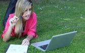 Mladý student venku v parku s počítačem a notebookem — Stock fotografie