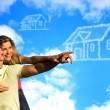 Happy coupleunder the blue sky dreaming of a house. — Stock Photo