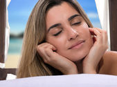Young woman relaxing on a beach bed — Stock Photo