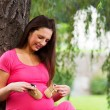 Pregnant woman sitting under a tree — Stock Photo