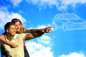 Couple pointing to clouds shaped like a car. — Stock Photo
