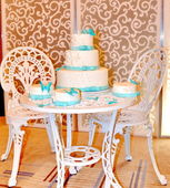 White and blue cakes on white table and two white chairs — Stock Photo