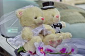 Wedding teddy bears sitting on car — Stock Photo