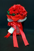 Red rose bouquet with bow tie on black background — Stock Photo