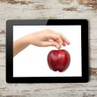 Tablet computer with the hand and a red apple on the screen — Stock Photo #19806849