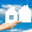 Two houses on the hand on blue sky background — Stock Photo #20130717