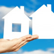 Two houses on the hand on blue sky background - Stock Photo