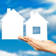 Two houses on the hand on blue sky background — Stock Photo #20887573